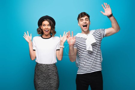 Photo for Excited man and woman waving hands and smiling at camera on blue background - Royalty Free Image