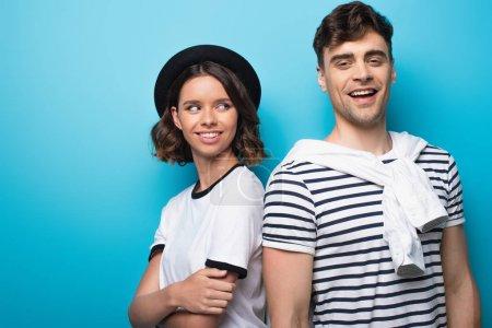 Photo pour Jeune femme gai restant près du petit ami de sourire sur le fond bleu - image libre de droit