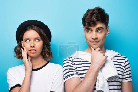 Photo pour Positif, jeune homme et femme souriant l'un à l'autre sur le fond bleu - image libre de droit