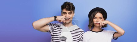 Photo pour Panoramic shot of cheerful man and woman holding fingers with drawn mustache near faces on blue background - image libre de droit