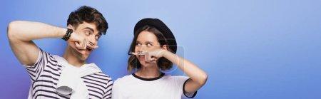Photo pour Plan panoramique de l'homme et de la femme positifs tenant les doigts avec moustache dessinée près des visages sur fond bleu - image libre de droit