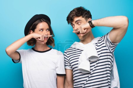 cheerful man and woman looking at each other while holding fingers with drawn mustache ner faces on blue background