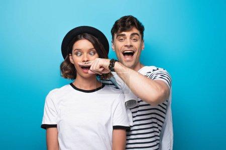 Photo pour Homme gai retenant le doigt avec la moustache tirée près du visage de la jeune fille sur le fond bleu - image libre de droit