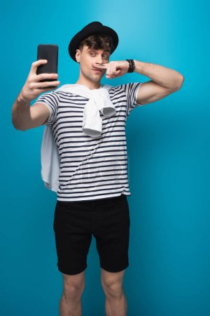Photo for Handsome man taking selfie with smartphone while holding finger with drawn mustache near face on blue background - Royalty Free Image