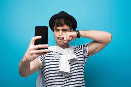 Photo for Tricky man taking selfie with smartphone while holding finger with drawn mustache near face on blue background - Royalty Free Image