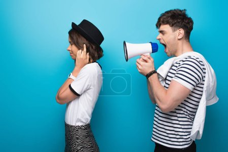 Photo for Angry man quarreling in loudspeaker at girlfriend plugging ears with fingers on blue background - Royalty Free Image