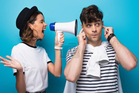 Photo for Angry girl quarreling in loudspeaker at boyfriend plugging ears with fingers on blue background - Royalty Free Image