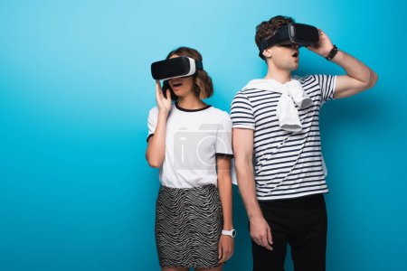 young, trendy man and woman using virtual reality headsets on blue background