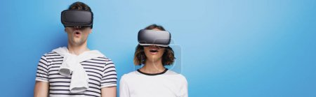 Photo for Panoramic shot of young man and woman using virtual reality headsets on blue background - Royalty Free Image