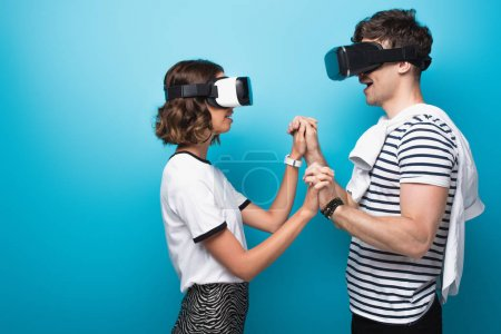 Foto de Young man and woman holding hands while using virtual reality headsets on blue background - Imagen libre de derechos