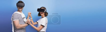 Photo pour Panoramic shot of young man and woman holding hands while using virtual reality headsets on blue background - image libre de droit