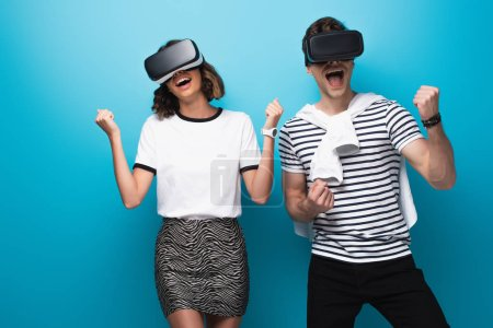 Photo for Cheerful man and woman dancing while using virtual reality headsets on blue background - Royalty Free Image