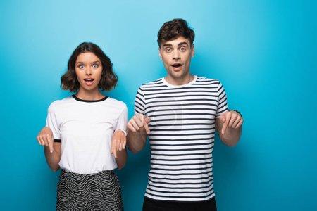 Photo pour Homme et femme étonnés pointant vers le bas avec des doigts et regardant l'appareil-photo sur le fond bleu - image libre de droit