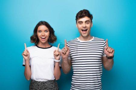 Photo pour Homme et femme gai pointant vers le haut avec des doigts et regardant l'appareil-photo sur le fond bleu - image libre de droit