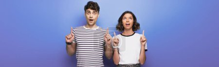 Foto de Panoramic shot of cheerful man and woman looking up and pointing with fingers on blue background - Imagen libre de derechos