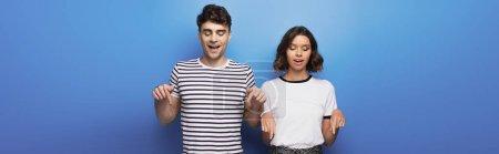 Photo pour Tir panoramique de l'homme et de la femme regardant vers le bas et pointant avec des doigts sur le fond bleu - image libre de droit