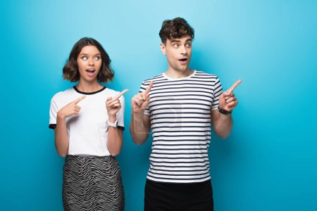 Photo for Cheerful man and woman looking away and pointing with fingers on blue background - Royalty Free Image