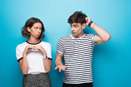 Photo for Discouraged man looking at offended girlfriend on blue background - Royalty Free Image