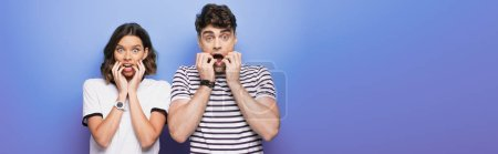 Photo for Panoramic shot of shocked man and woman looking at camera on blue background - Royalty Free Image