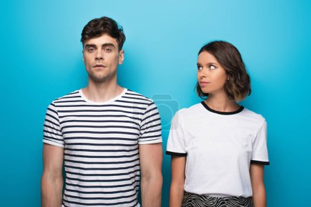 Photo for Positive young girl looking at offended boyfriend on blue background - Royalty Free Image
