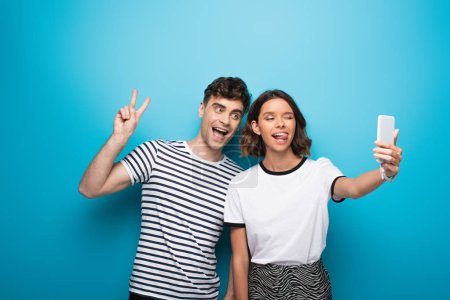 Photo for Cheerful girl sticking tongue out while taking selfie with cheerful man showing victory sign on blue background - Royalty Free Image