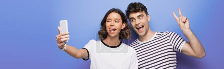 Photo pour Panoramic shot of cheerful girl sticking tongue out while taking selfie with cheerful man showing victory sign on blue background - image libre de droit