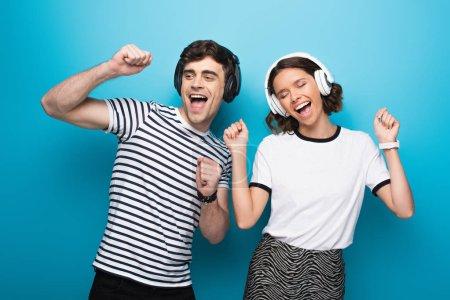 Photo pour L'homme et la femme excités dansant tout en écoutant la musique dans le casque sur le fond bleu - image libre de droit