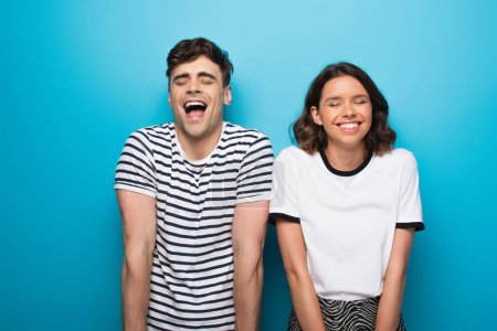 Photo for Excited man and woman laughing with closed eyes on blue background - Royalty Free Image