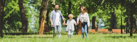 Photo for Back view of family holding hands and running in park during daytime - Royalty Free Image