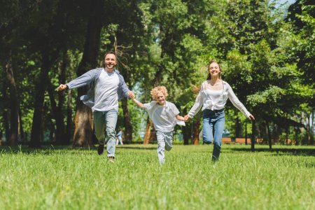Photo for Excited family holding hands and running in park during daytime - Royalty Free Image