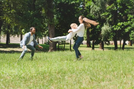 family spending time together, mother spinning son in park during daytime