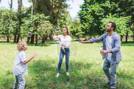 Photo pour Mother, father and son playing with soap bubbles in park during daytime - image libre de droit