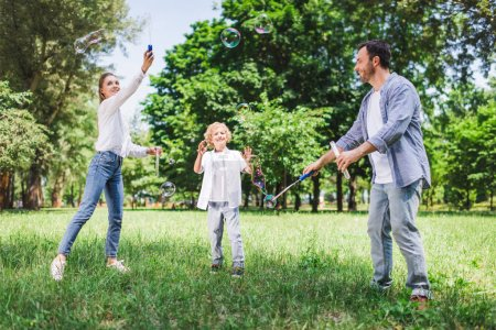 Photo for Mother, father and son in casual clothes playing with soap bubbles in park - Royalty Free Image