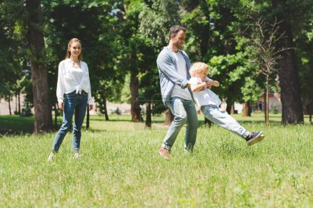 Photo for Family spending time together, father spinning son in park - Royalty Free Image
