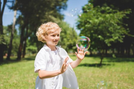 Photo for Adorable boy Gesturing near soap bubbles in park - Royalty Free Image