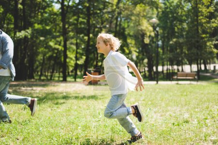 Photo for Happy son running with father in park during daytime - Royalty Free Image