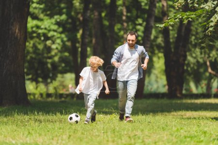 father and adorable son playing football in park together