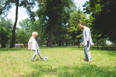 Photo for Father and adorable son playing football in park together - Royalty Free Image