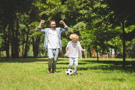 excited father and adorable son playing football in park