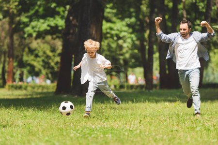 Photo for Cheerful father and adorable son playing football with soccer ball in park - Royalty Free Image