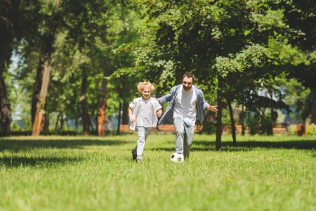 Photo for Father and adorable son playing football with soccer ball in park - Royalty Free Image