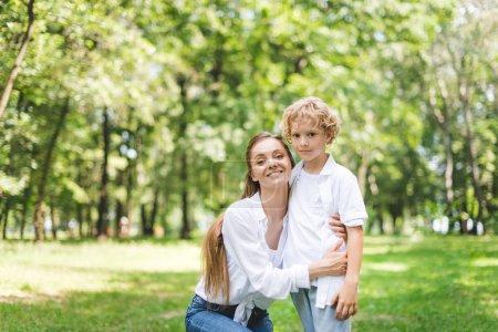 Foto de Beautiful smiling mom hugging son in park and looking at camera - Imagen libre de derechos