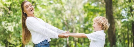 Photo for Panoramic shot of beautiful smiling mom and son holding hands in park - Royalty Free Image