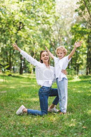 Photo for Beautiful smiling mom and son with Raised Hands in park looking at camera - Royalty Free Image