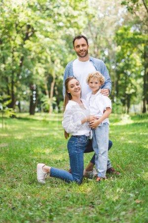 Photo pour Famille heureuse regardant l'appareil-photo et posant dans le stationnement - image libre de droit