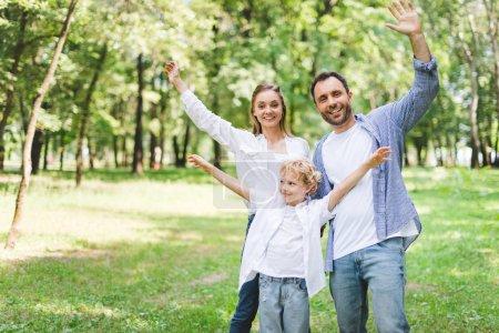Foto de Familia emocionada con las manos extendidas mirando la cámara en el parque - Imagen libre de derechos