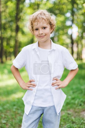 Photo for Cute happy boy with Hands On Hips in park looking at camera - Royalty Free Image