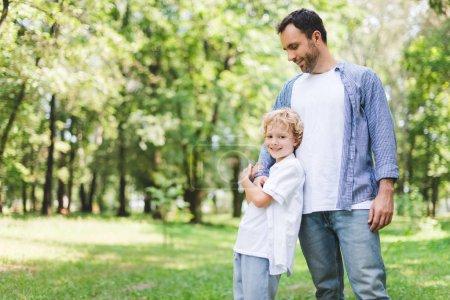 Photo pour Beau père étreignant le fils adorable dans le stationnement avec l'espace de copie - image libre de droit