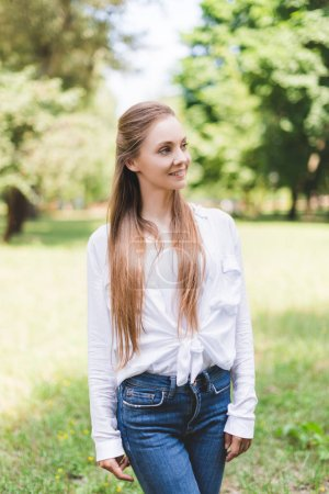 Photo for Beautiful smiling woman in park looking away - Royalty Free Image