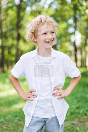 Photo for Cute happy boy with Hands On Hips in park looking away - Royalty Free Image